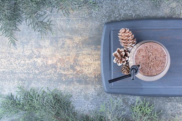Una tazza di bevanda deliziosa con pigne e paglia su tavola scura. foto di alta qualità