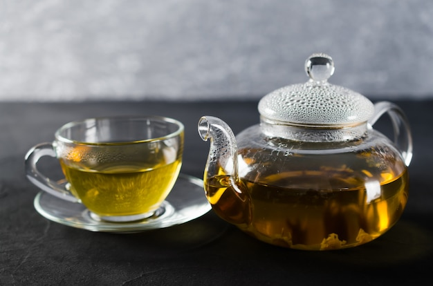 Cup of delicious herbal tea and glass teapot.
