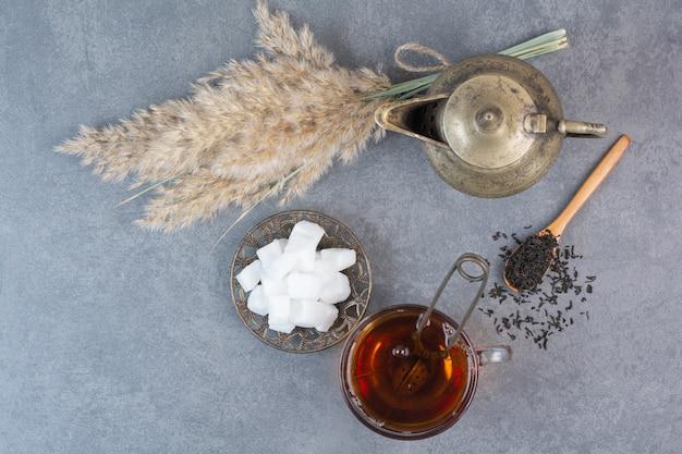 Una tazza di tè delizioso con bollitore antico e zucchero.
