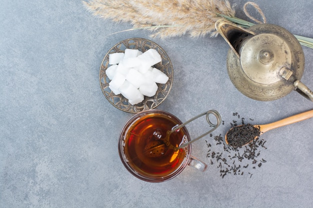 A cup of delicious tea with ancient kettle and sugar