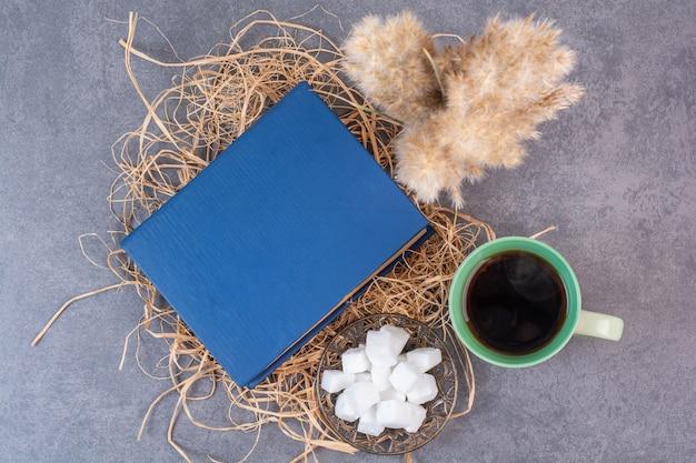 Una tazza di tè delizioso con il libro e lo zucchero sul fieno.