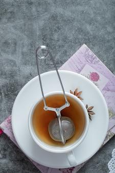 Una tazza di tè delizioso con anice stellato sulla zolla bianca.