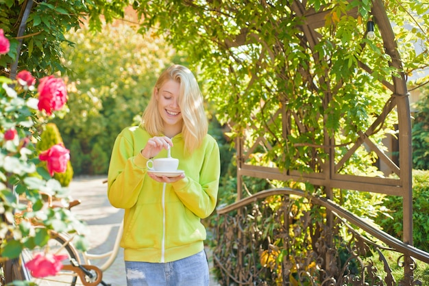 Cup of delight. hedonism and gourmet. enjoy delicious creamy cappuccino in blooming garden. girl drink gourmet cappuccino. woman enjoy divine taste of cappuccino alone. coffee lover. pure enjoyment.