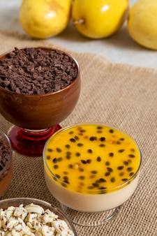 Cup of dessert with milk chocolate mousse and white chocolate shavings, ganache mousse and passion fruit mousse.