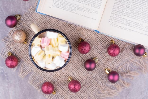 Una tazza di bevanda con marshmallow e palle di natale rosse intorno