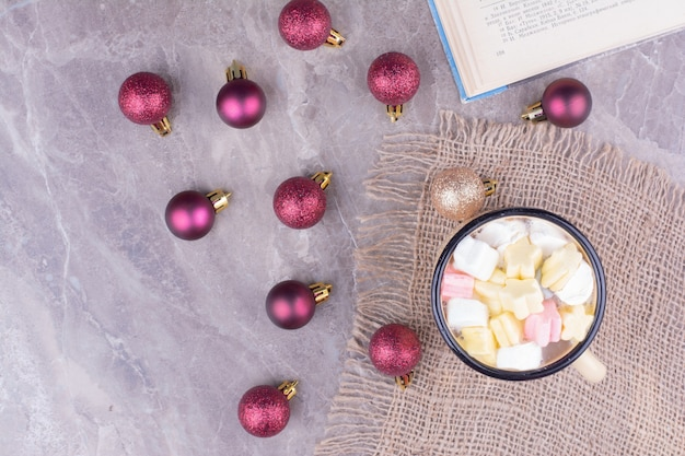 A cup of drink with marshmallows and red christmas balls around