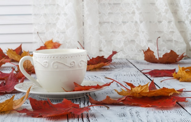 Cup of english tea with milk on white table with maple leaves