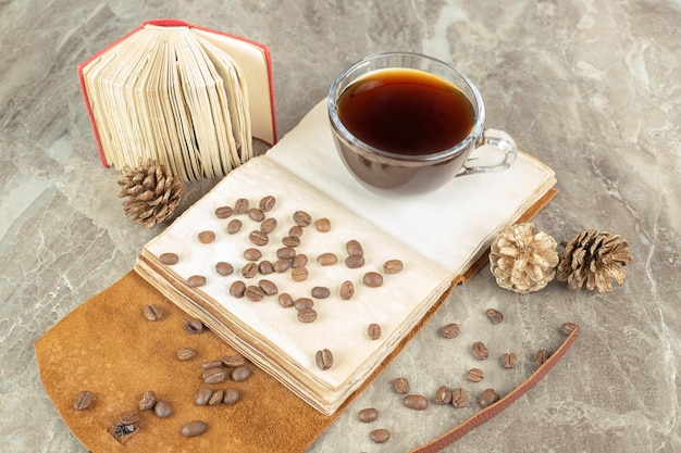 Cup of espresso and coffee beans on open notebook