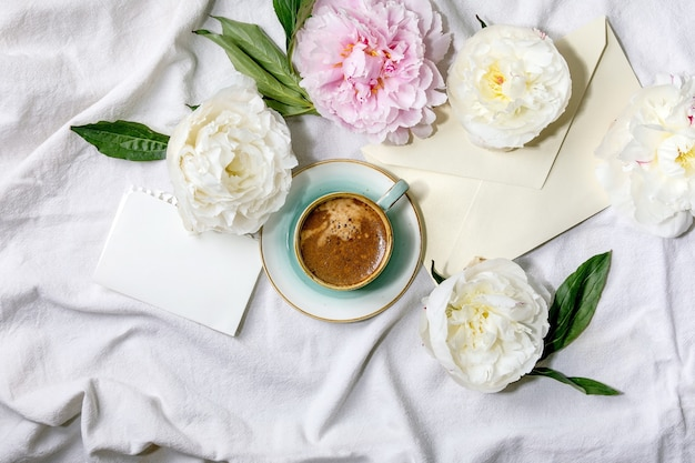 Cup of espresso coffee, blank paper, envelope, pink and white peonies flowers with leaves over white cotton textile surface