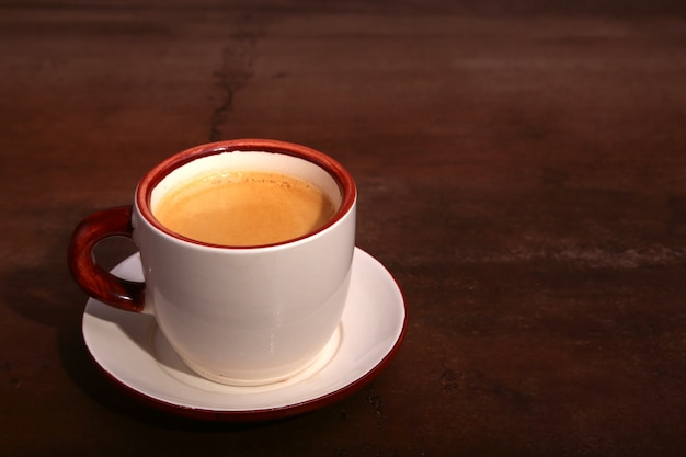 A cup of espresso coffee on a dark wooden surface