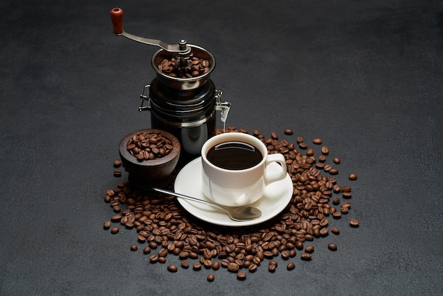Cup of espresso coffee and hand grinder on roasted brown coffee beans on concrete table