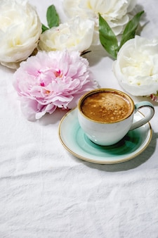 Cup of espresso coffee, pink and white peonies flowers with leaves. flat lay, copy space