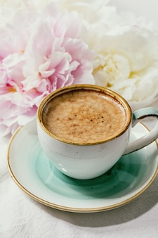 Cup of espresso coffee, pink and white peonies flowers with leaves over white cotton textile surface