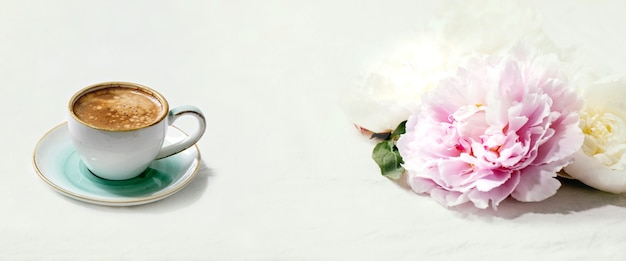 Cup of espresso coffee, pink and white peonies flowers with leaves over white cotton textile table. flat lay, copy space
