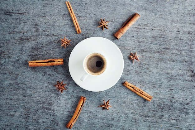 A cup of espresso coffee on a saucer, cinnamon sticks and anise