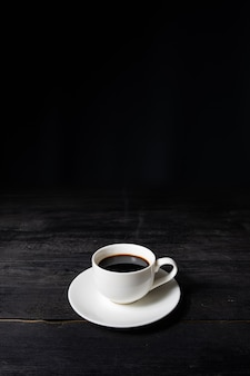 Cup of espresso coffee on vintage black table, front view. coffee in white cup on dark surface with pleasant old wood texture