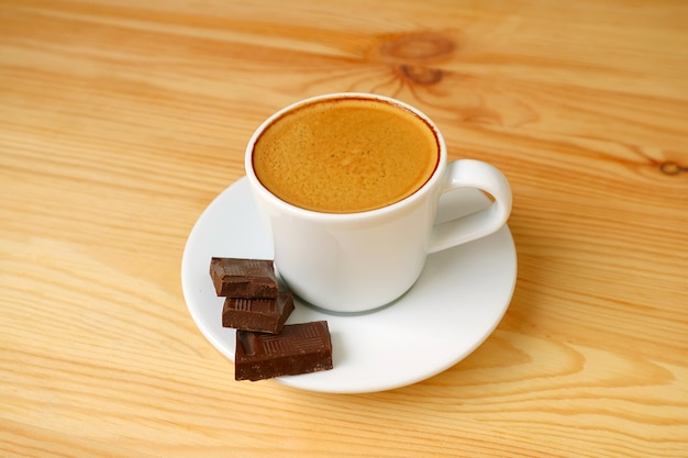 Cup of espresso coffee with dark chocolate cubes isolated on wooden table
