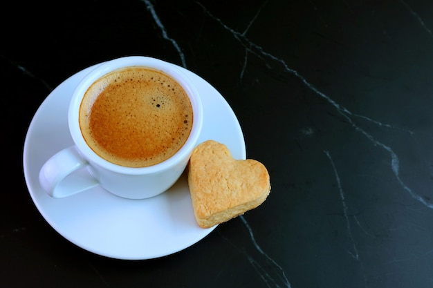 Cup of espresso coffee with a heart shaped butter cookie on black table