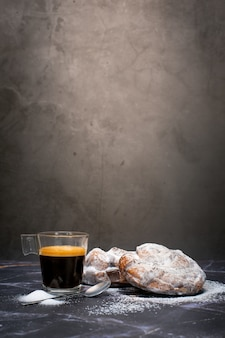 Cup of espresso coffee with two chocolate croissants and icing sugar covering