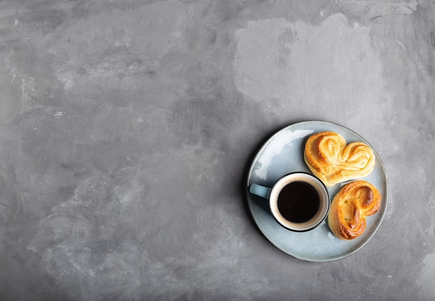 Cup of espresso coffee with two heart-shaped sweet buns in plate on gray concrete. minimalist still life. top view.