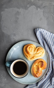 Cup of espresso coffee with two heart-shaped sweet buns in plate on gray concrete surface. minimalist still life. top view. space for text.