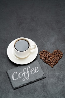 Cup of espresso and heart shaped roasted coffee beans on dark concrete table