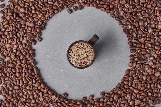 A cup of espresso in the middle of coffee beans.