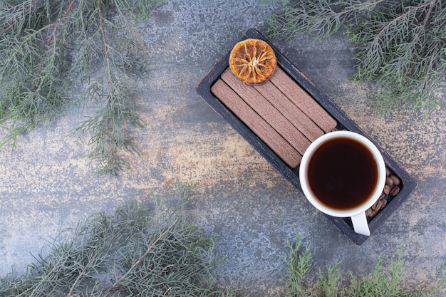 Cup of espresso, stick biscuits and coffee beans on black plate. high quality photo