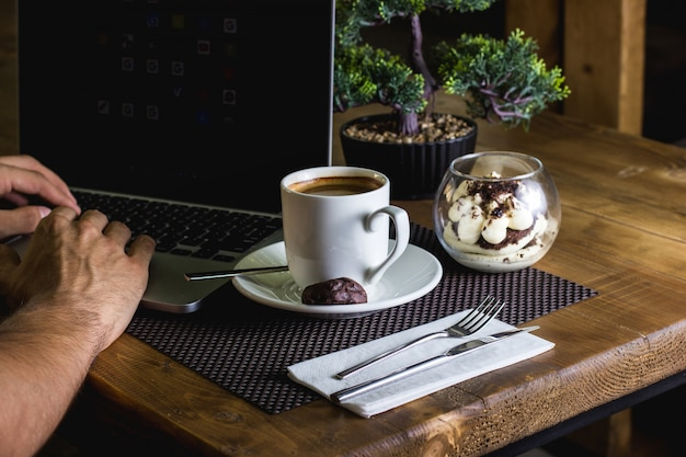A cup of espresso and tiramisu served for man working in his notebook