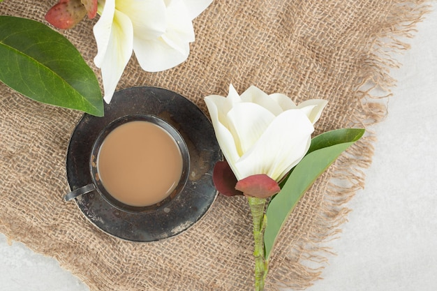 Cup of espresso and white flowers on burlap.