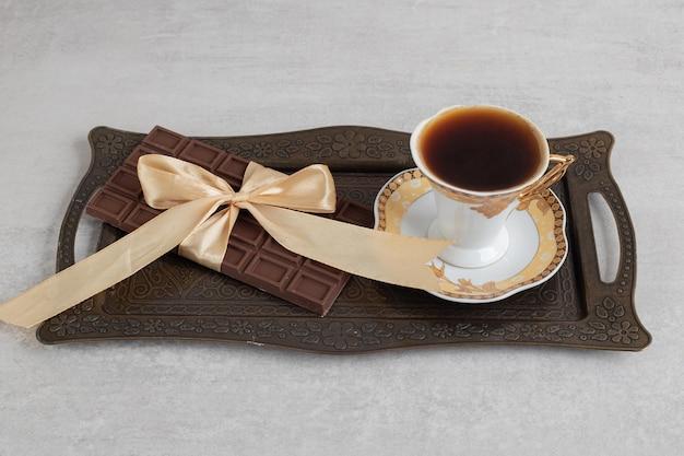 Tazza di caffè espresso con barretta di cioccolato legata con nastro sul vassoio