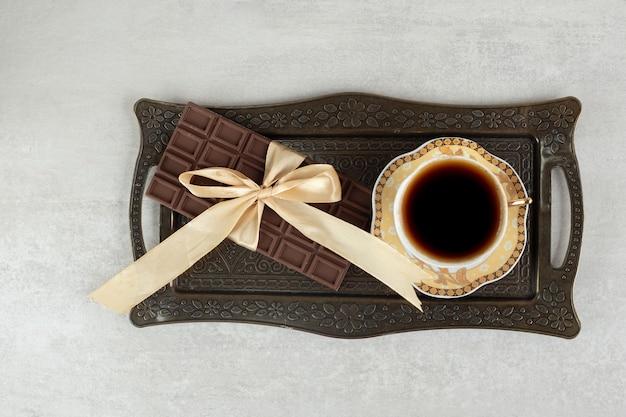 Tazza di caffè espresso con tavoletta di cioccolato legata con nastro sul vassoio
