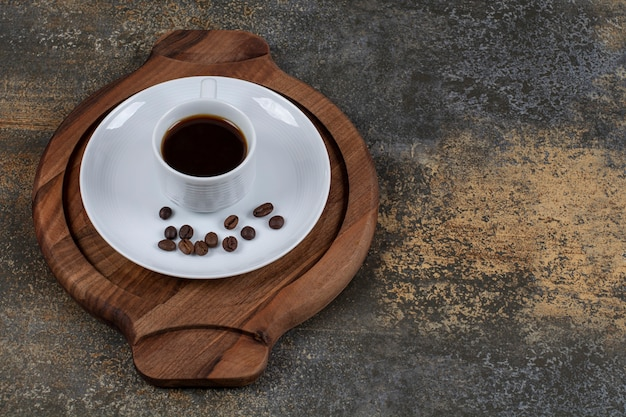 Cup of espresso with coffee beans on wooden board.