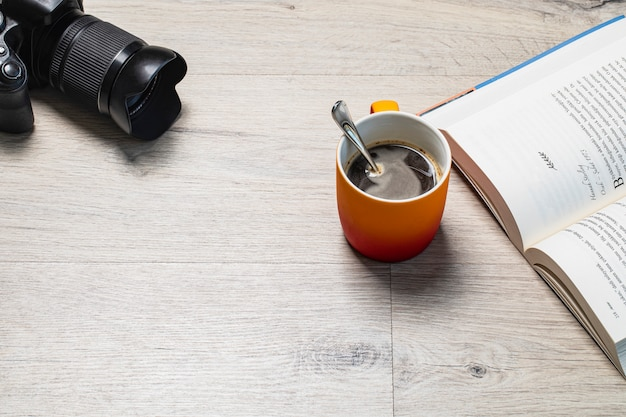 A cup of espresso with a good book and a photo camera around