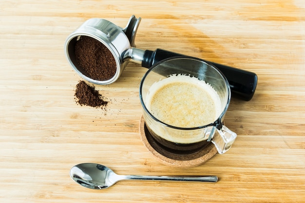 Cup of espresso on wooden board with ground coffee