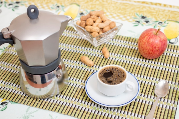 Cup of expresso coffee with peanuts and fruit