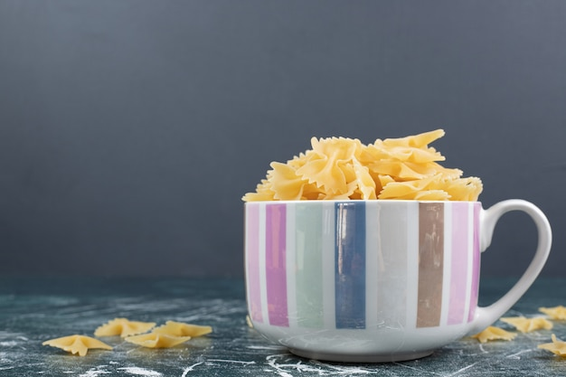 Cup of farfalle pasta on blue background. high quality photo