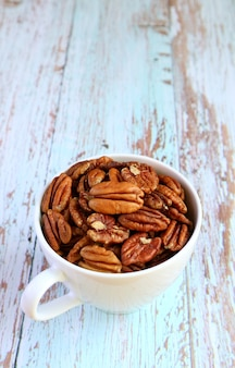 A cup filled with dried pecan nuts isolated on pale blue wooden table