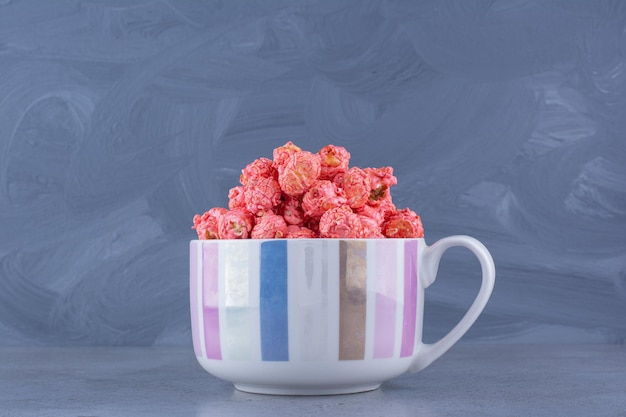 Cup filled with red popcorn candy on marble surface