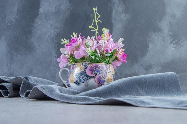 Una tazza di fiori su un pezzo di stoffa, sul tavolo bianco.