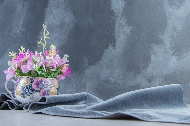 A cup of flowers on a piece of fabric, on the white table.