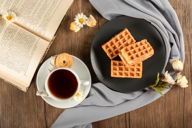 A cup fo tea and waffles in a saucer