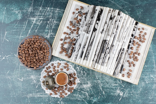 Cup of foamy coffee, plate of coffee beans and book on marble table.