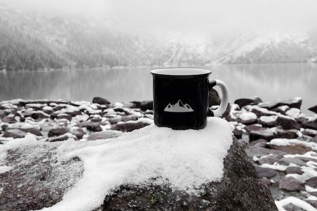 碑文のためのカップ。冬の山の湖の背景に黒のマグカップ