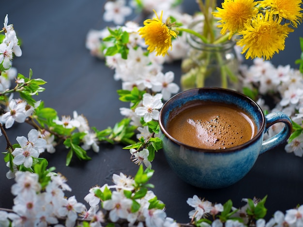 A cup of fragrant coffee, cherry blossoms, blooming yellow dandelions