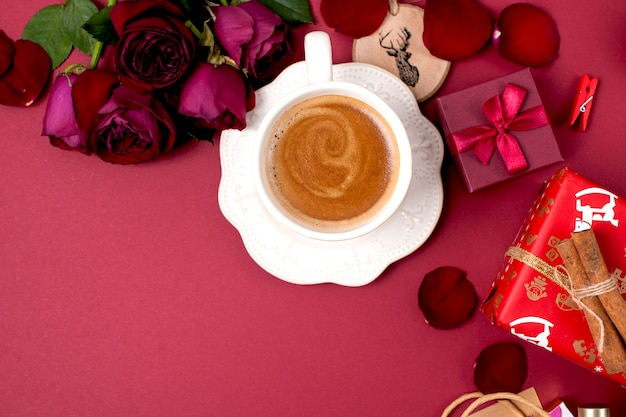 A cup of fragrant coffee and christmas decoration. roses, gifts and christmas surprises. top view. frame. copy spase