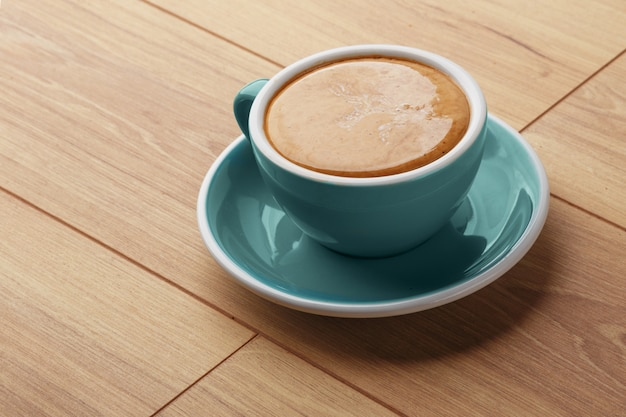 A cup of fragrant coffee in foam on a wooden table.
