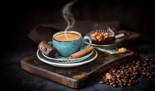 A cup of fragrant coffee on the of a rustic board with coffee beans and chocolate cake, a hot drink