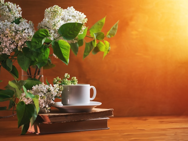 A cup of fragrant tea or coffee, a blooming white bouquet of lilacs and old books. copy space morning breakfast