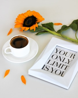 Cup of fresh americano or espresso coffee with flower and motivation words frame on white table background.